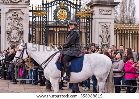 London, England - December 20, 2015 - Female Metropolitan Police Officer on horseback during Changing of the Guard at Buckingham Palace London, England - stock photo