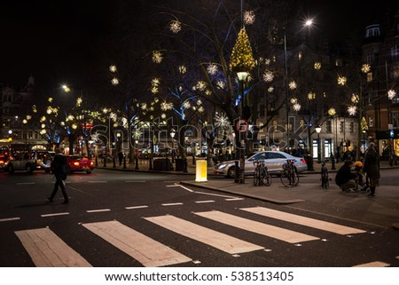 London, England - 17 December 2016: Night view of Sloane Square with Christmas light decorations and people crossing the road in Chelsea, London, UK.