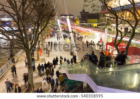 LONDON, ENGLAND - December 16, 2016: People walking in the Christmas market in the Southbank Centre. The old style market is located between Waterloo Bridge and the London Eye.