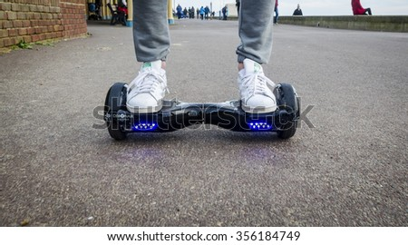London, England - December 28, 2015: Person Riding a HoverBoard on a Public Footpath, They are now banned in all public places in the United Kingdom.  - stock photo