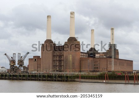 LONDON, ENGLAND - DECEMBER 28, 2011:  Silhouette of Battersea Power Station viewed from the bank of the Thames. Power Station is being redeveloped by an international consortium. - stock photo