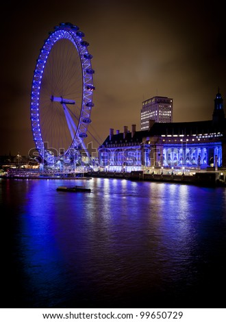LONDON, ENGLAND FEB 17: London eye at night with Westminster Bridge and Parliament on Feb 17, 2012 in London, United Kingdom. - stock photo