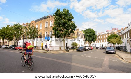 London, England - July 14, 2016: A cyclist passes terraced town houses in a prosperous residential neighbourhood of Islington in North London.