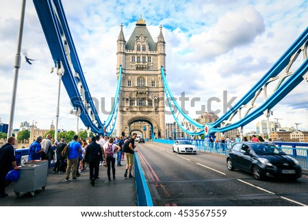 LONDON, ENGLAND - JULY 16,2016. People and transportation on London's Tower bridge, an iconic symbol of London, England.   - stock photo