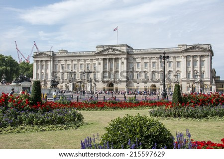 London, England - July 29th 2014: Tourists gather at the gates of Buckingham Palace. The flag flies to show the Queen is in residence - stock photo