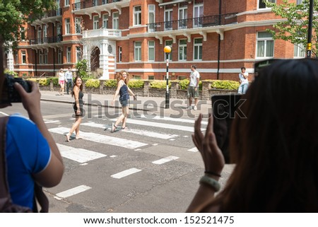 LONDON, ENGLAND - JULY 17: Tourists photograph as people walk the pedestrian crossing in famous Abbey road as tyhe beatles did in 1960's on Abbey Road in London July 17, 2013. - stock photo