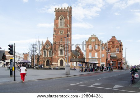 LONDON, ENGLAND - MARCH 15, 2014: Centre of Acton, West London with shoppers.  The church of St Mary dominates the centre of the suburb. - stock photo