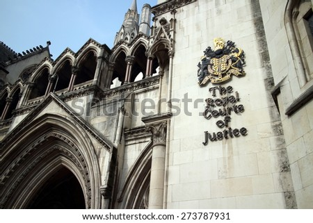 London, England - March 17, 2015: Part of the exterior facade of the Royal Courts of Justice in London, England showing the coat of arms of the courts and architectural details - stock photo