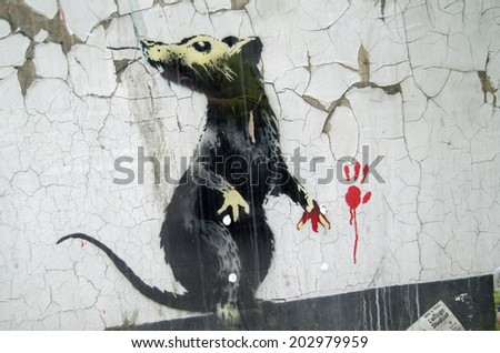 LONDON, ENGLAND - MAY 17, 2014: A rat, caught red handed.  Detail of a piece of graffiti art painted by Banksy on a street in Central London.   - stock photo