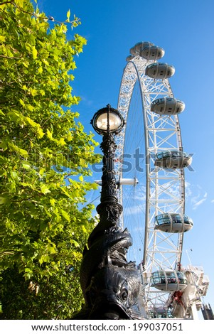 London,England - May 25,2014:London Eye and street lamp  at the edge of the River Thames. The London Eye is also known as the Millennium Wheel. It was built in 1999 and is 443 feet tall. - stock photo