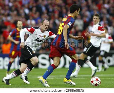 LONDON, ENGLAND. May 28 2011: Manchester's forward Wayne Rooney and Barcelona's midfielder Sergio Busquets during the 2011 UEFA Champions League final between Manchester United and FC Barcelona - stock photo