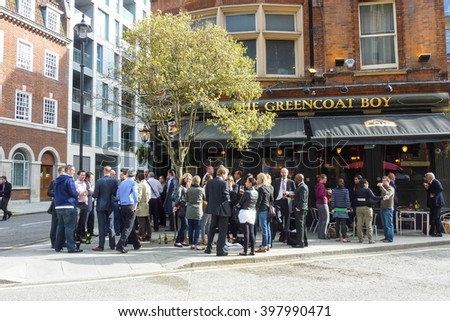 LONDON, ENGLAND - MAY 13, 2011: People drinking in front of a typical pub in the city center. The name pub comes from public house and is a drinking establishment fundamental to the British culture.