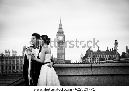 LONDON - ENGLAND 25 OCTOBER 2015 - Picture of bride and groom with Big Ben and the The Houses of Parliament as they embrace each other during an overcast day in LONDON ON OCTOBER 2015.