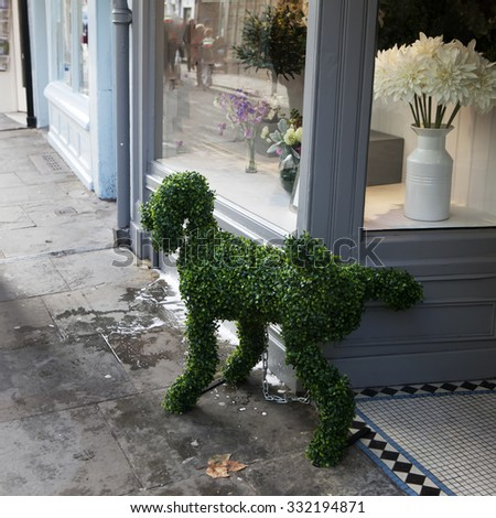 LONDON, ENGLAND - OCTOBER 29, 2013: The Dog from artificial grass, lifts his foot on the street near the flower shop - stock photo
