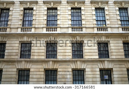 London, England - Sept 09, 2015: External view of rows of windows on a building in Whitehall, London, England. Whitehall in Westminster is home to many of the UK government departments  - stock photo