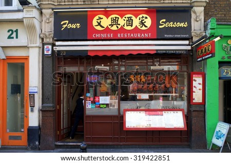 London, England - Sept 09, 2015: Person entering a Chinese Restaurant doorway in a Chinatown street in London, England. There are more than eighty restaurants in the Chinatown District. - stock photo