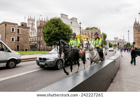 LONDON, ENGLAND - SEPTEMBER 15, 2013:  The Metropolitan Police with special police horses to keep the crowds under control, they sauntering around London - stock photo