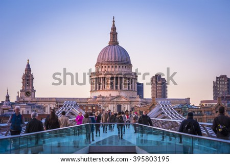 London, England - St.Paul's Cathedral and Millennium Bridge with Londoners walking through at sunset - stock photo