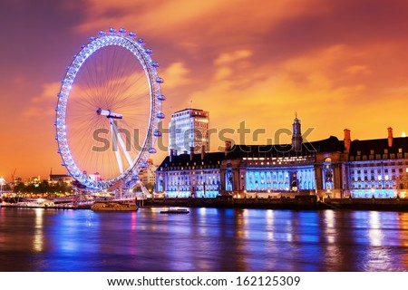 London, England the UK skyline in the evening. Ilumination of the London Eye and the buildings next to River Thames - stock photo