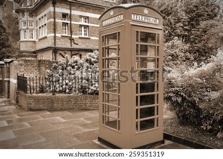 London, England - typical telephone booth. Sepia tone - filtered vintage photo style. - stock photo