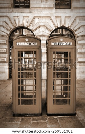 London, England - typical telephone booths. Sepia tone - filtered vintage photo style. - stock photo