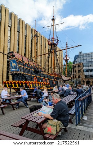 LONDON, ENGLAND, UK - JULY 1, 2014: People are resting near to the Replica of Golden Hind (Francis Drake famous galleon) docked in St Mary Dock, The Thames River, London.  - stock photo