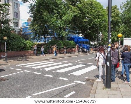 LONDON, ENGLAND, UK - JUNE 18: People crossing the Abbey Road zebra crossing made famous by the 1969 Beatles album cover on June 18, 2011 in London, England, UK - stock photo