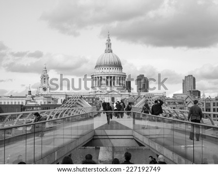 LONDON, ENGLAND, UK - MARCH 04, 2009: Tourists crossing the Millennium Bridge linking the City of London with the South Bank between St Paul Cathedral and Tate Modern art gallery