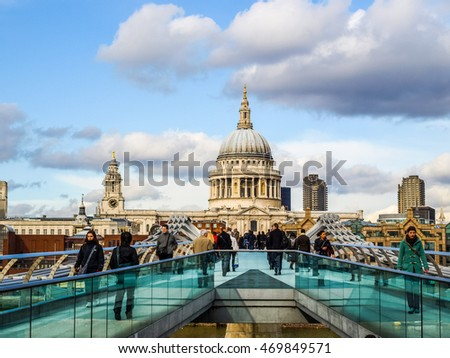 LONDON, ENGLAND, UK - MARCH 04, 2009: Tourists crossing the Millennium Bridge linking the City of London with the South Bank between St Paul Cathedral and Tate Modern art gallery (HDR)