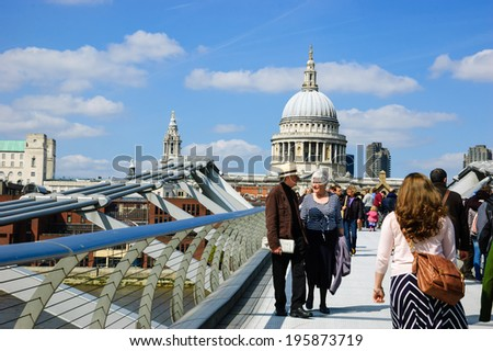 LONDON, ENGLAND, UK - MAY 3, 2014: Tourists walking across the Millennium Bridge, which was opened in 2000. St Paul's cathedral is seen at backgrounds.