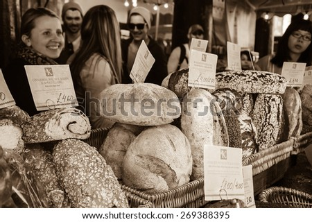 LONDON, ENGLAND, UK - MAY 3, 2014: Unidentified young people purchase bread at Karaway bakery in famous Borough Market. In last decades Borough Food Market became a fancy tourist attraction. - stock photo