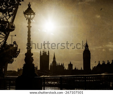 London, England - View of the Houses of Parliament and Big Ben taken from across the Thames River with the London Eye in the foreground. Photo taken at sunset with vintage reto filter effect applied. - stock photo