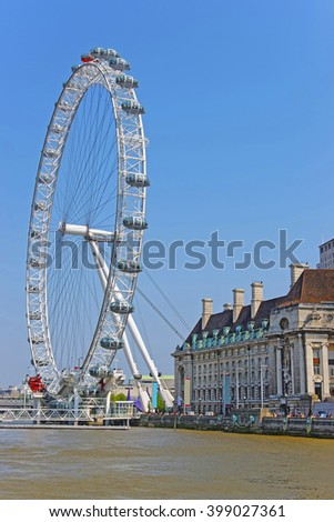 London Eye and County Hall near River Thames in London, UK. London Eye is a giant Ferris wheel on South Bank of River Thames. County Hall is a building which was headquarters of London County Council - stock photo