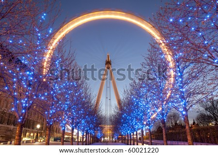 London Eye at twilight and blue lighting decoration on trees. At a height of 135m, it is the tallest Ferris wheel in Europe. - stock photo