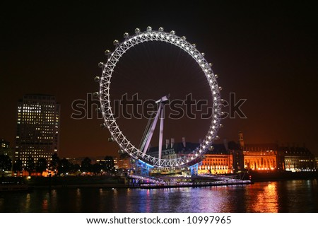 London eye - London landmark. Survey Wheel in night illumination over the Thames river - stock photo