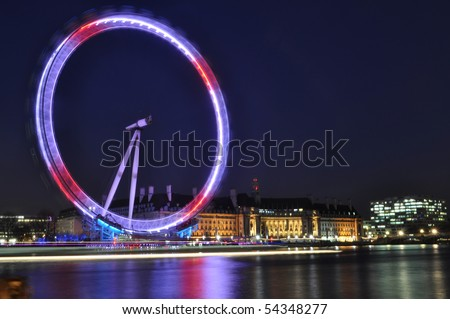 LONDON EYE, UK - May 25: London Eye at night with reflection from the River Thames May 25, 2010, UK - stock photo