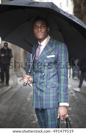 LONDON - FEBRUARY 18: The man wears the suit in check with umbrella poses for photographers outside Somerset house during London Fashion week on February 18, 2014.