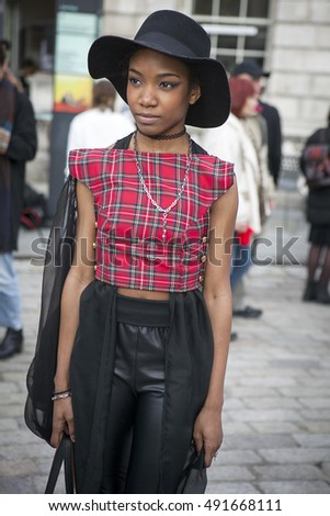 LONDON - FEBRUARY 18: Woman in red shirt with black hat poses for photographers outside Somerset house during London Fashion week on February 18, 2014. Mango style
