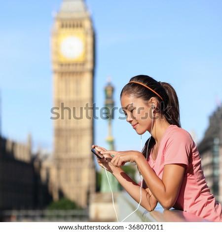 London fitness lifestyle woman listening to running music playlist on smartphone. Female resting after training in urban city street. Runner girl near Big Ben, Westminster Bridge, London, England, UK - stock photo