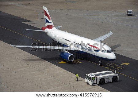 LONDON GATWICK AIRPORT SOUTHERN ENGLAND UK - APRIL 2016 - A passenger jet and tug using a taxiway which has just been resurfaced - stock photo