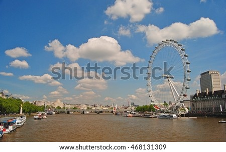 LONDON, GREAT BRITAIN - MAY 15, 2014. Thames River waterfront with the London Eye, cruising boats, bridge and boats in the distance.