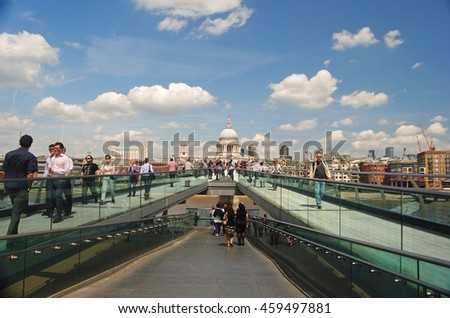 LONDON, GREAT BRITAIN - MAY 19, 2014. View of cross section of the Millennium Bridge in London, toward St Pauls Cathedral, with people. - stock photo