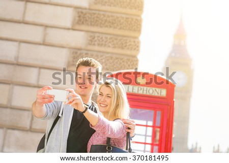 London, happy young couple taking a selfie with a red phone booth and Big Ben on background. They are on holidays for valentines day or they are enjoying their honeymoon. - stock photo