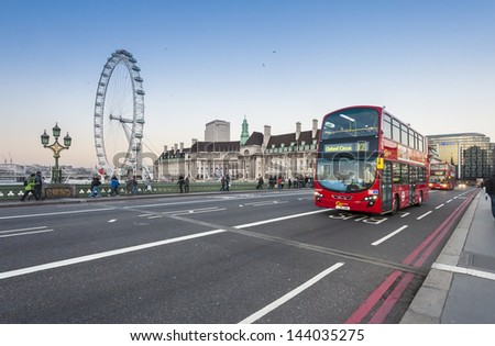 LONDON - JAN 21: London Buses and London Eye on January 21, 2012 in London, England. The London Bus service is one of the largest urban bus networks in the world with 8,000 buses covering 700 routes. - stock photo