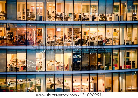 LONDON - JAN 31: people work in an office building in London on January 31, 2013. Full-time employees in the UK work longer hours than the EU average, according to the Office for National Statistics. - stock photo