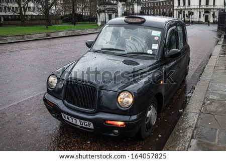 LONDON - JANUARY 08: A black cab next to Buckingham Palace on January 08, 2013 in London. The London's iconic black cabs are a symbol of the city and a major attraction in themselves. - stock photo