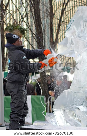 LONDON - JANUARY 13: A unidentified member of the African Ice Sculpting Team working on their Sculpture for the Annual London Ice Sculpting Festival, Canary Wharf, on January 13, 2012 in London, UK. - stock photo