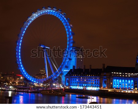LONDON - JANUARY 19: Night shot of the London Eye on January 19, 2014 in London. The London Eye is a  Ferris wheel situated on the banks of  river Thames. The  structure is 135 m tall.                 - stock photo