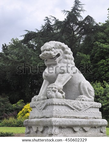 LONDON - JULY 4, 2016. An ancient Chinese stone guardian lion sculpture weighing 10 tons overlooks the lake in Kew Gardens, London, UK. - stock photo