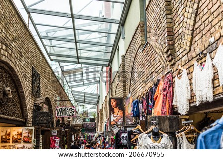 LONDON - JULY 5: Camden Lock market, famous alternative culture shops pictured on July 5th, 2014 in Camden Town, London. Camden Town markets are visited by 100,000 people each weekend.  - stock photo